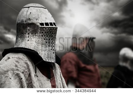 Side View Of Medieval Knight In Iron Helmet Posing. Selective Focus Of Brave Man Standing Outdoors W