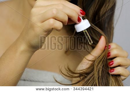 Woman Applying Oil On Dry Hair Ends Or Sun Protection Concept. Split Hair Tips. Oiling Hair Before W