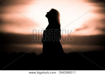 Youth Woman Soul At Golden Sun Meditation Dreaming Past Times. Silhouette In Front Of Sunset Or Sunr