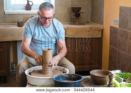 Pottery Concept. Professional Ceramist Working With Clay At Throwing Table In Workshop, Studio.