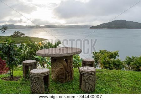 Stone Table With Indigenous Art Overlooking Lake Arenal In Costa Rica. Surrounded By Green Pasture A