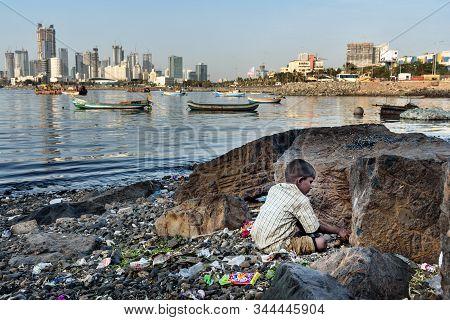 Mumbai, India - February 27, 2019:young Boy On The Coast Of Sea Near Haji Ali Dargah With Skyline On