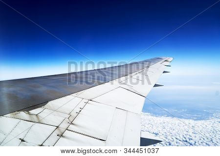 View From Airplane Window Engine And Wing Flying Above The Clouds