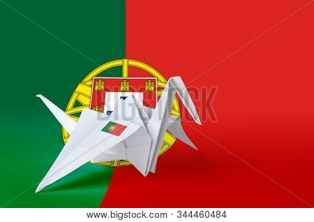 Portugal flag depicted on paper origami crane wing. Handmade arts concept poster