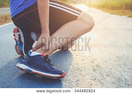 Injury From Workout Concept : Asian Man Use Hands Hold On His Ankle While Running On Road In The Par