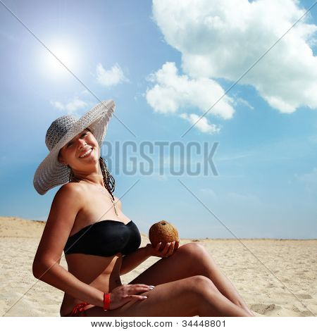 Woman Drinking On The Beach From The Coconut