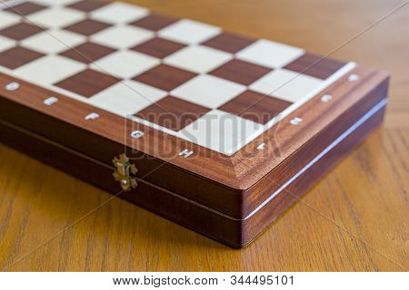 Closed Checkerboard Close-up. Closed Chessboard For Chess Game On Wooden Table