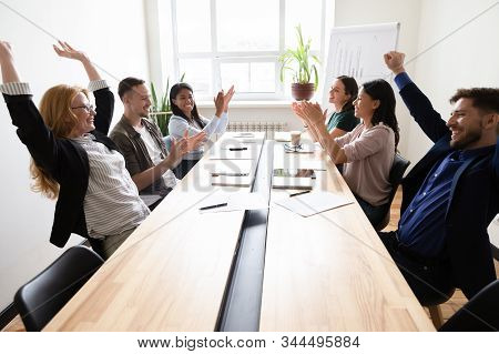 Happy Corporate Staff Celebrating Shared Success Seated At Boardroom Desk