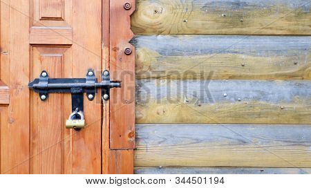 Old Wooden Door With A Black Metal Bolt. Close Up View Of A Lock And Latch On A Wooden Door. Rustic