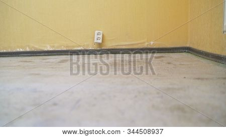 Primed Floor In The Room. The Worker Primed The Floor With A White Primer. Apartment Repair. Fill Th