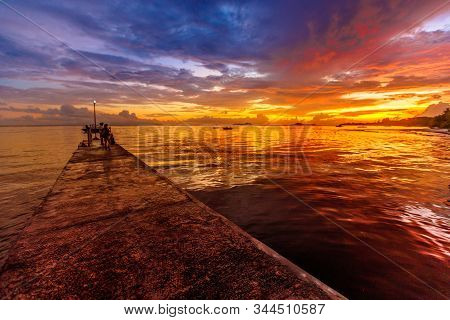 Wooden Pier With Sunset Sky Reflected In The Tropical Sea. Grand Anse Fond De Lanse Beach On Indian