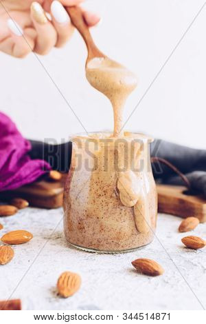 Almond Nut Butter In Glass Jar. Homemade Raw Organic Almond Nuts Paste On White Background. Healthy
