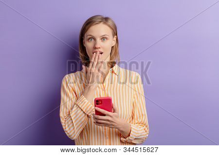 Portrait Of Beautiful Shocked, Surprised Woman After Receiving Message From Friend, Holding Smartpho