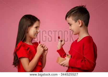 Happy Little Couple Girl And Boy With Red Hearts Isolated On Pink Background. Child Boy And Girl Wan