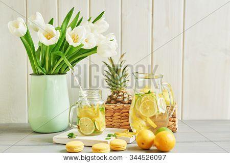 Lemonade And Flowers Tulips On Table.mason Jar Glass Of Lemonade With Lemons And Straw. Copy Space.f