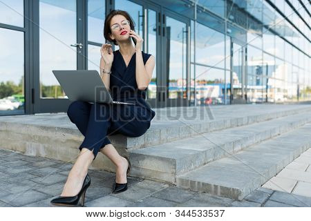 Business Concept. Close-up Of An Attractive Young Business Woman With Red Lips With A Laptop Sitting