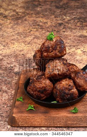 Stack Of Cooked Homemade Meatballs In Cast Iron Skillet