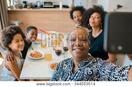 Multigenerational Family Taking Selfie With Phone At Home.