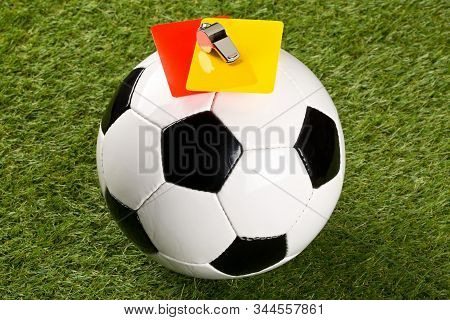 Soccer Ball With Referee Yellow And Red Cards And Chrome Whistle On Top Over Grass Background - Pena