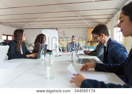 Group Of Busy Business Partners During Morning Briefing. Focused Workers Sitting At Table And Discus