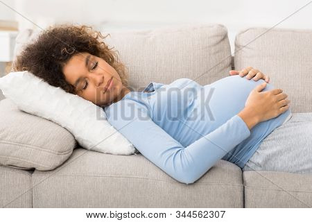 Tranquil Pregnant Woman Sleeping On Back And Embracing Belly, Lying On Sofa
