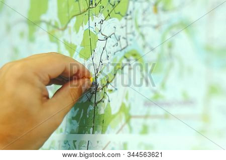 Mark A Point On The Map With Your Hand. Topographic Map.