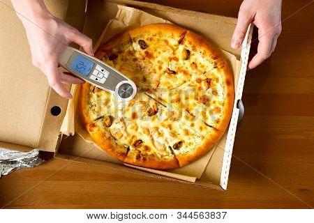 Measuring Pizza Temperature With A Thermometer. Delivered Pizza In A Box, Delicious Pizza.