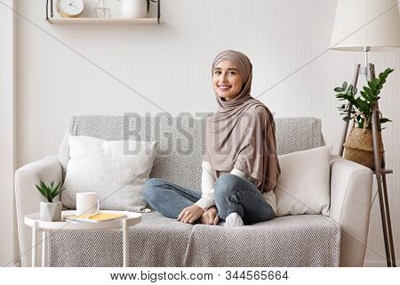 Portrait Of Beautiful Muslim Girl In Hijab Sitting On Sofa At Home And Looking At Camera, Resting In