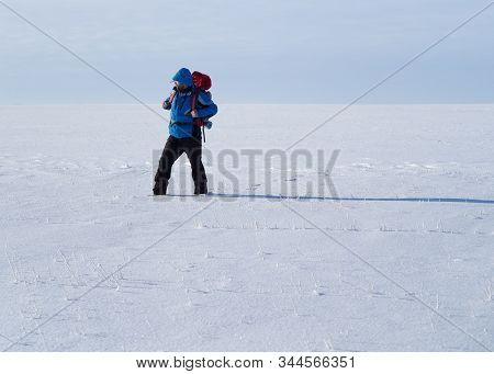Lonely Backpacker Walking Throw Snow Desert. Surviving Anh Hard Travel Concept.