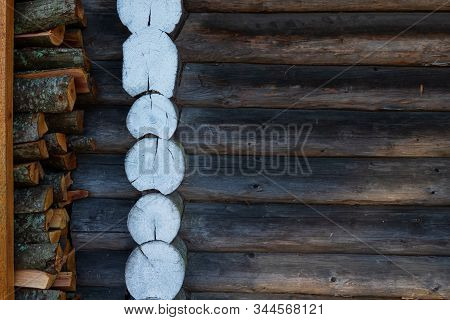 Fragment Of A Wooden Wall Of An Old Rustic Bathhouse. There Are Ends Of Logs Of White Color, A Part