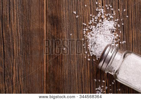 Salt Close Up. Scattered Salt And Salt Shaker On A Wooden Table Top View. Salt Shaker With Salt On A