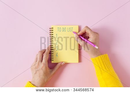 To Do List In Spiral Notepad. Woman Hands Making To Do List In Notebook. Spiral Notepad With Pencil