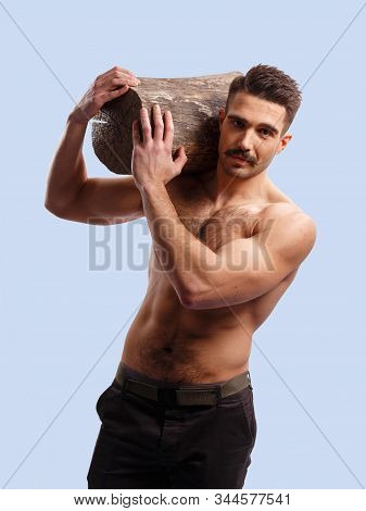 Slim Man With Moustache, With Naked Torso, Holding A Wooden Log On His Shoulders, Looks At Camera On