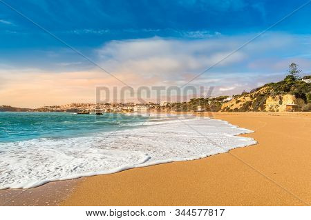 Wave Foam On Sandy Beach In Albufeira Resort Village, Popular Touristic Destination In Algarve, Port
