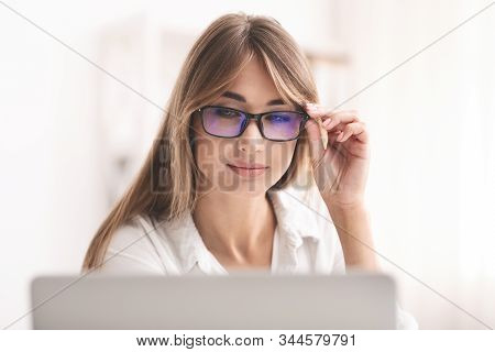 Poor Sight. Business Lady In Eyeglasses Squinting Eyes Looking At Laptop Screen Working At Computer