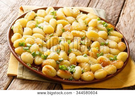 Oil-fried Potato Dumplings Gnocchi With Garlic, Cheese And Green Onions Close-up On A Plate. Horizon