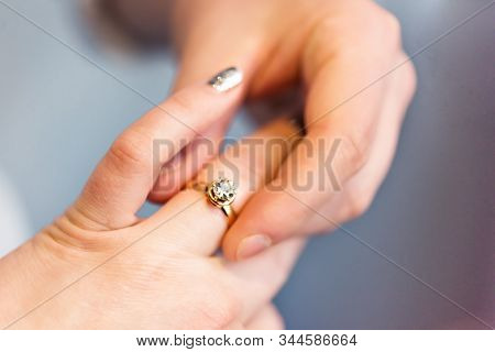 Groom Put Engagement Ring On His Bride Finger. Jewellery Diamond Ring In Husband To Be Hands. He Put