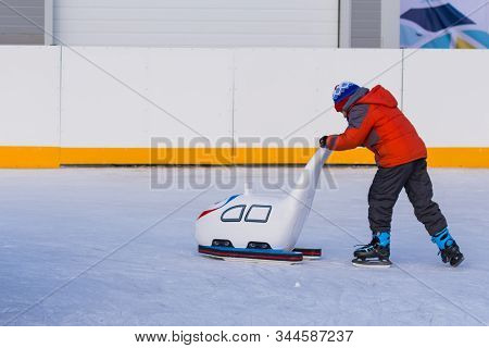 A Little Boy Is Learning To Ride On Figure Skates Using A Special Training Support Equipment. Winter