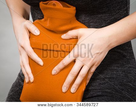 Unrecognizable Woman Having Strong Stomach Ache. Female Suffer On Belly Pain, Holding Hot Red Water