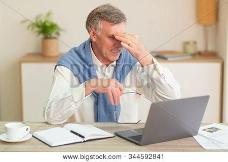 Eyestrain In Old Age. Senior Man Massaging Aching Eyes Holding Eyeglasses Working On Laptop Computer