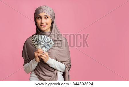 Ready For Shopping. Pensive Arabic Woman In Hijab Holding Dollar Cash And Thinking How To Spend Mone