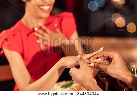Romantic Proposal. Unrecognizable Afro Man Proposing Putting On Engagement Ring On Womans Hand Havin
