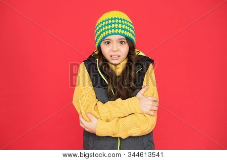 It Might Be Too Cold To Trek Outside. Little Child Feel Cold Red Background. Small Girl Shiver In Co