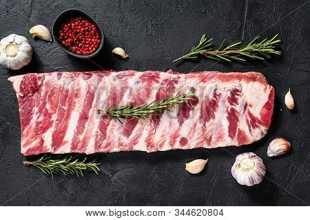 Rack Of Raw Pork Spare Ribs Seasoned With Spices. Black Background. Top View