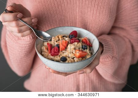 Woman In Cozy Pink Sweater Eating Oatmeal Porridge With Berries. Concept Of Healthy Eating, Healthy