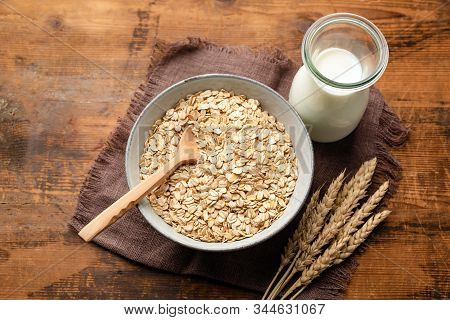 Dry Oat Flakes, Oatmeal, Rolled Oats And Bottle Of Oat Milk On A Wooden Background. Healthy Vegan, V