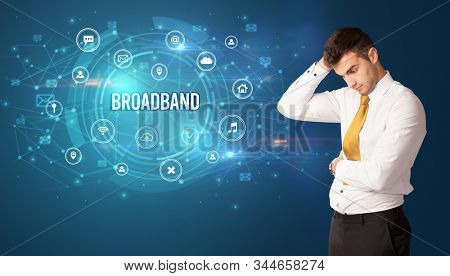 Businessman thinking in front of technology related icons and BROADBAND inscription, modern technology concept