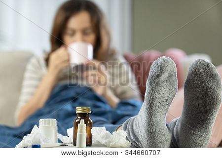 Sick Woman Drinking Tea Sitting On Sofa At Home. She Is Suffering From Influenza Or Colds.