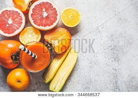 Orange, Carrots, Grapefruit And Persimmon Juice In A Glass And Ingredients For Smoothie Background,