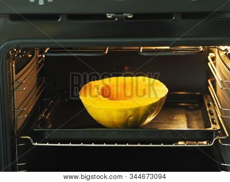 Cooking Pumpkins On A Black Baking Sheet In The Oven. Home Kitchen. Natural Food. Traditional Autumn